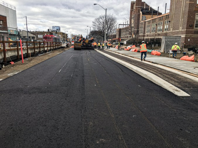 Fresh pavement is put down along a route.