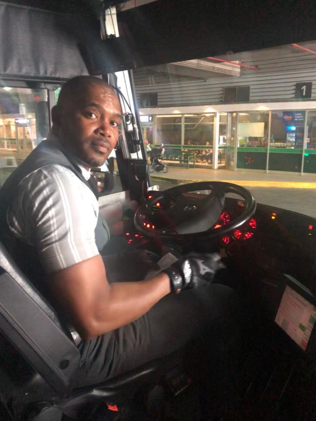 A bus driver sits behind the wheel.