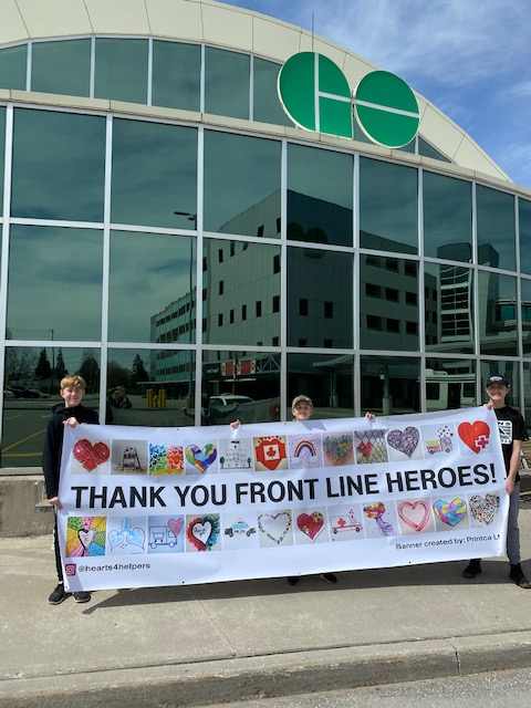 The boys hold up the banner outside a GO station.