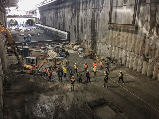 Crew stands at bottom of a large pit.
