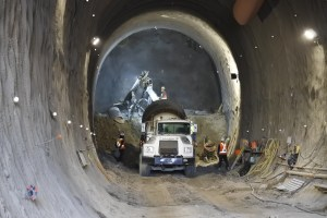 Image shows a tunnel, with crews working by worklights inside.