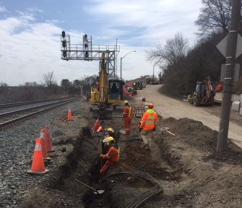 Construction crews relocating cables in advance of the track installation