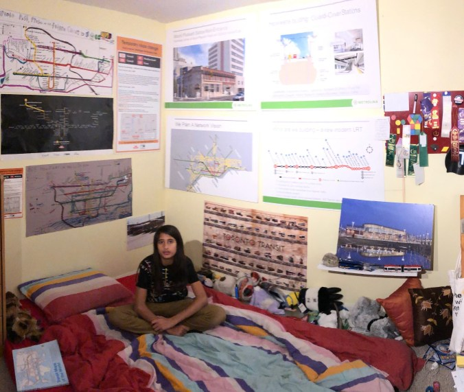 The inside of a bedroom with walls decorated with transit related material.