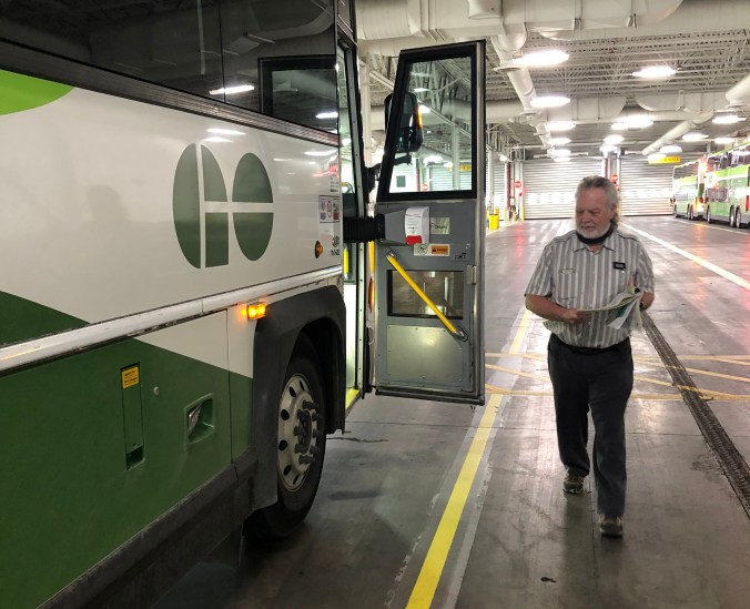 Bus driver inspecting the exterior of the GO bus before departing the garage