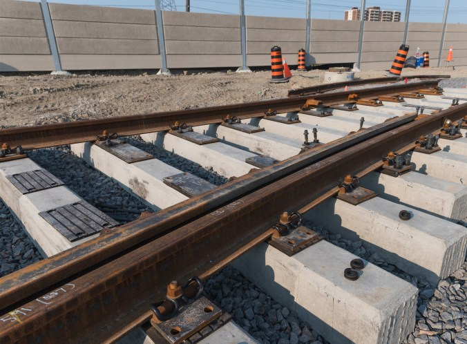 Image shows a line of new rails on concrete support.