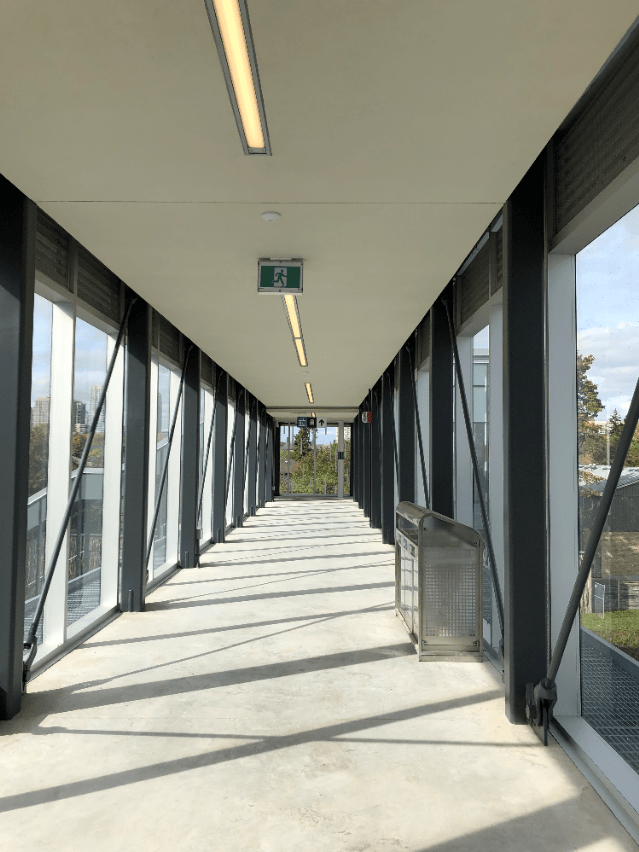 Image shows the inside of a pedestrian bridge, with glass on both sides.