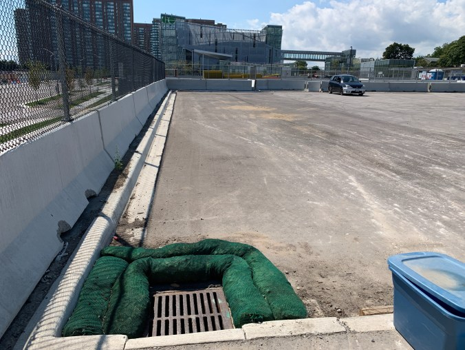 Image shows green sandbags around a drain in a parking lot.