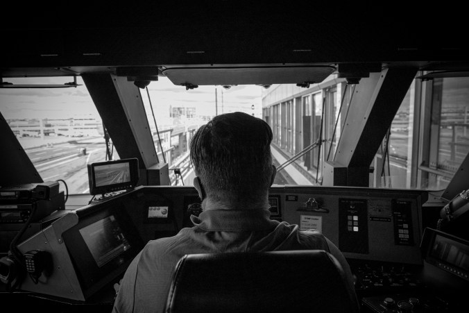A man sits at the controls of an UP vehicle.
