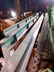 Workers put in large girders over a roadway.