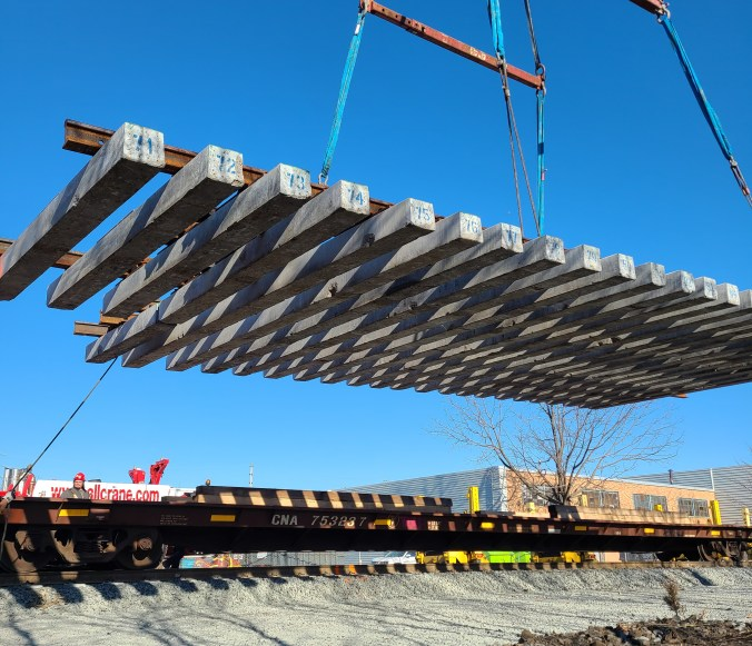 A large section of track is offloaded by a large crane.