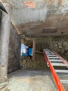 Image shows a ladder heading into a pit.