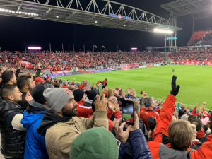 Fans cheer during a soccer game.