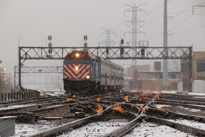 view of the tracks during the day in winter, with gas fired flames on to keep switches clear in Chicago  and a train in the background