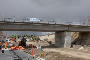 Image shows workers under a bridge.