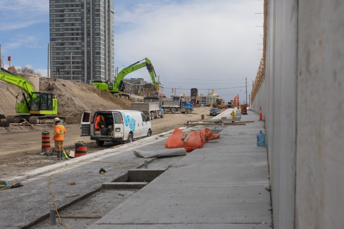 Image shows construction site next to a large wall.