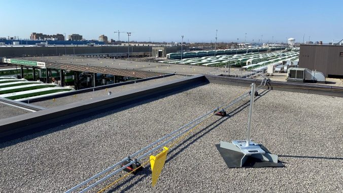 view from the roof of the train facility with the new warning lines installed and trains in the distance