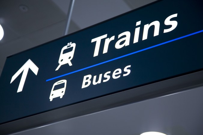 Image shows a train and bus sign.