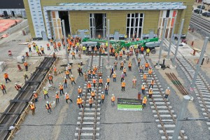 Image shows workers gathered near tracks.