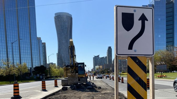 An excavator works along Hurontario street to remove the concrete medians that run along the middle of the road.
