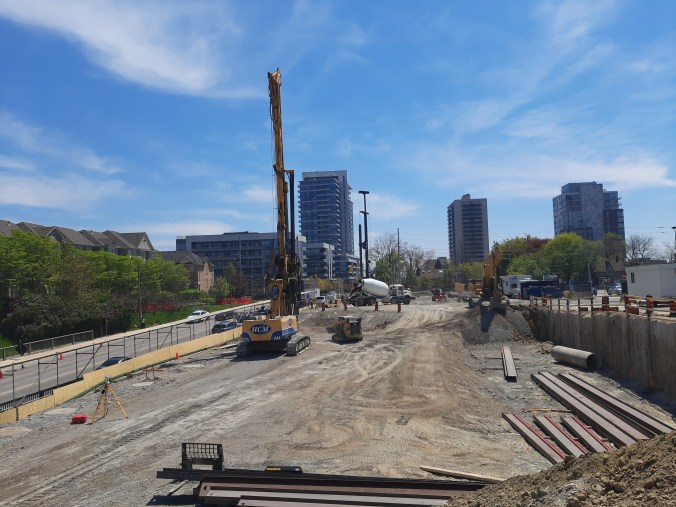 Image shows a construction site with buildings in the background.