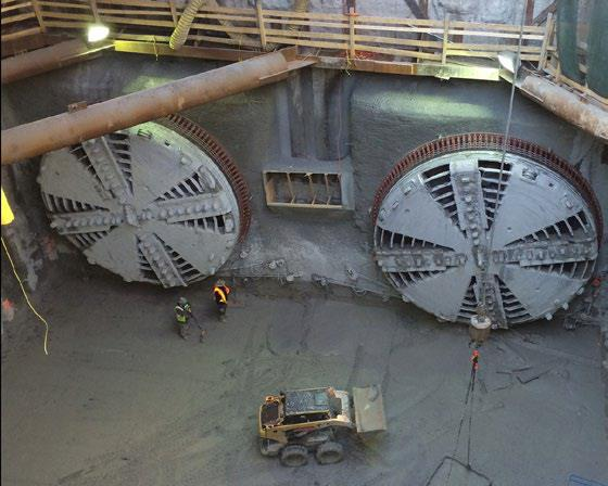 Image shows crews toiling near large TBMs.