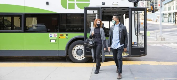 two people get off a GO bus with the yellow safety lines behind them.