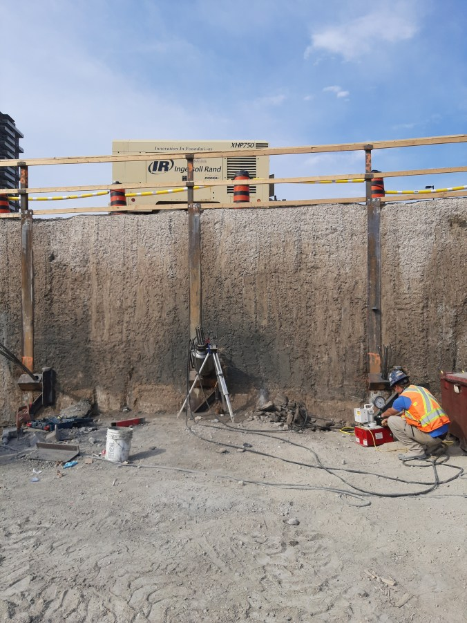 Image shows a man working against a wall.