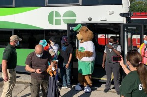 GO Bear stands by a bus.