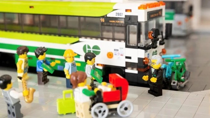 LEGO GO bus sit in model GO bus terminal with LEGO people waiting to board