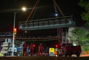 Crews watch as a section of bridge is moved in.