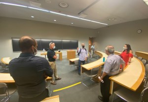 Image shows people talking inside a room.