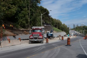 Image shows a dump truck next to a retaining wall.