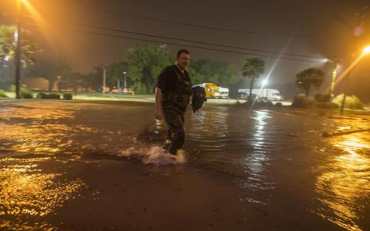 Person walking in flooding caused by tropical depression Nate