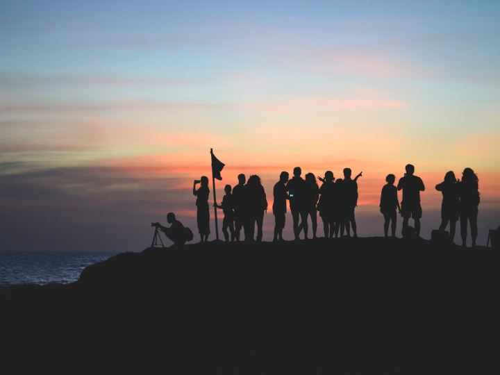 silhouettes of people standing on top of a hill with a flag