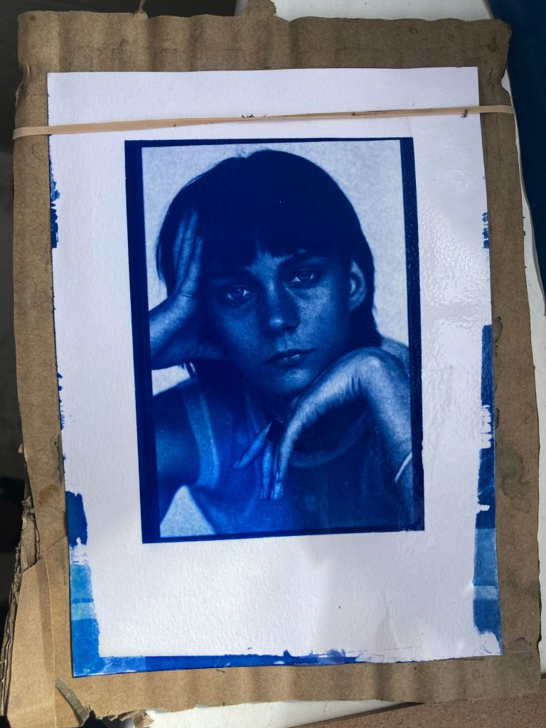 The completed cyanotype photographic print drying on a piece of cardboard it has been attached to with a rubber band
