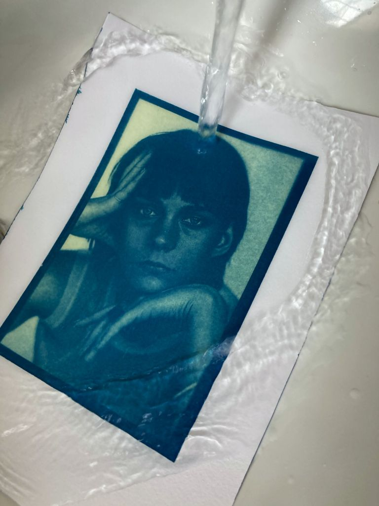 Water pouring over an exposed cyanotype print, the image appearing
