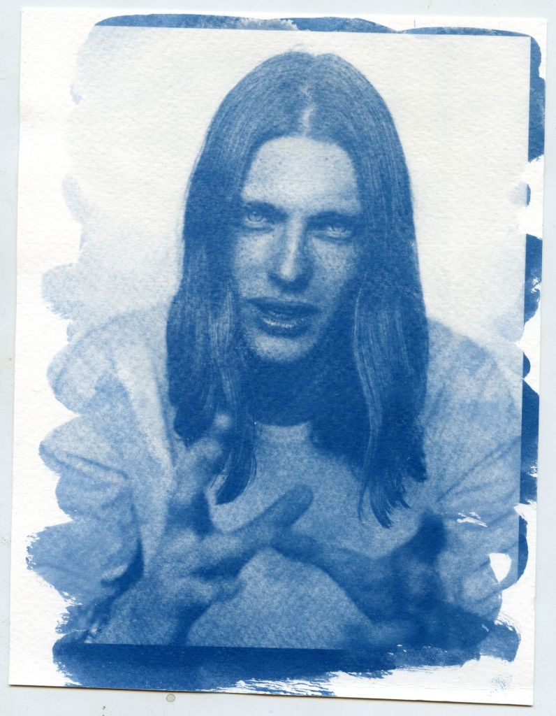 A Photographic Cyanotype Print of a man with long hair.