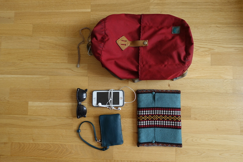 Small flat purse, phone, sunglasses and day bag packed in device compartment