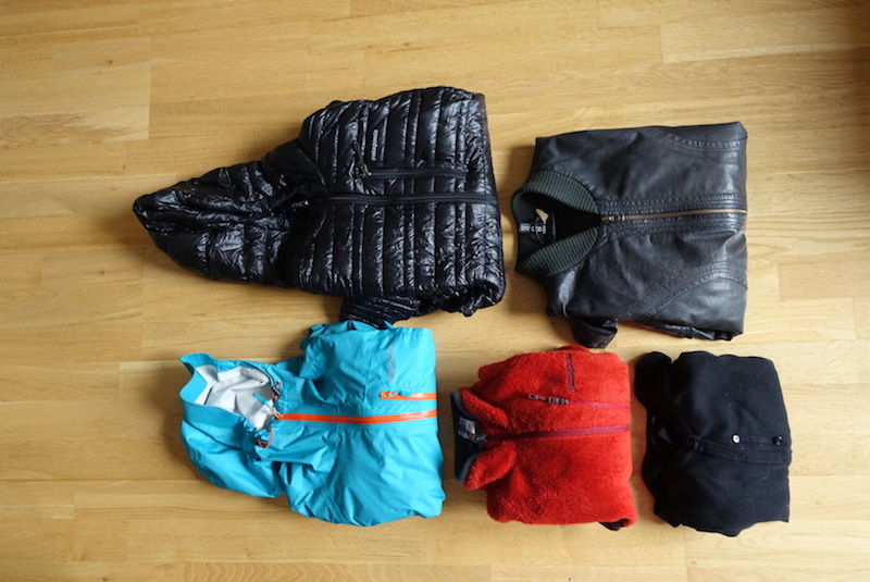 Travel gear and outerwear packed into the main compartment of the Minaal Carry-on