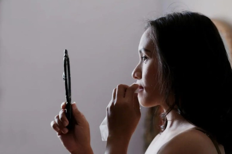 Woman looking into a handheld mirror