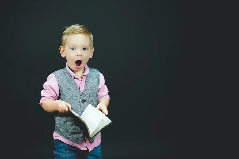 A surprised boy with a book