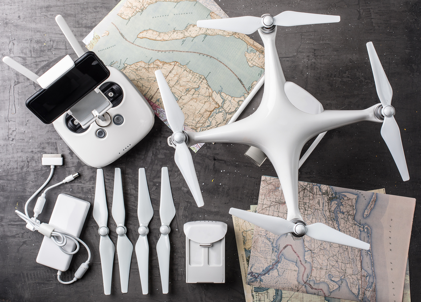 drones, a drone resting on top of a map, extra parts and controller on table