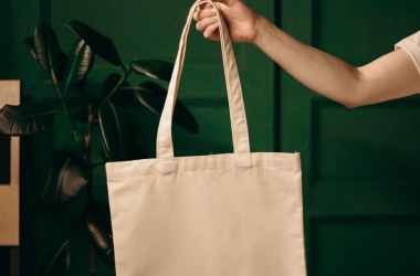 person holding white tote bag