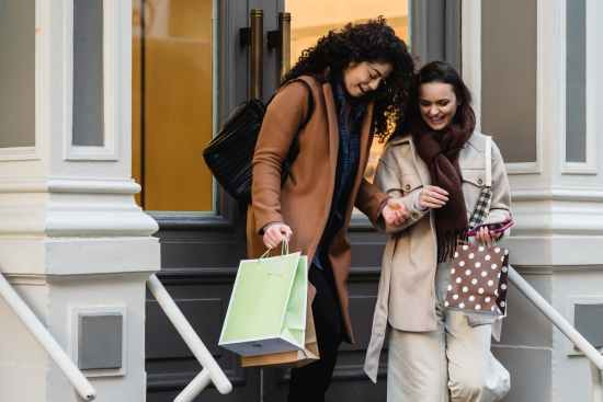 cheerful multiethnic women with shopping bags walking out of store