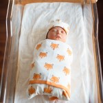 Newborn baby Charlie swaddled in a Monica + Andy blanket right after being born.
