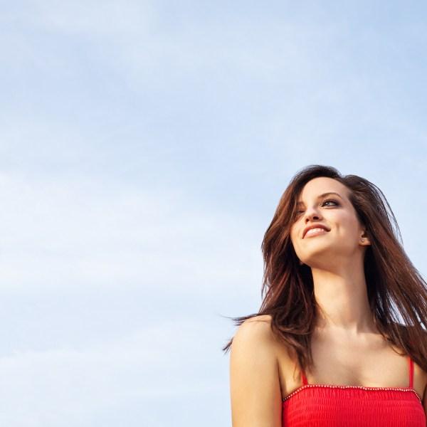 Essere te stessa. Il primo passo per amarti. Immagine di una donna felice, con un cielo azzurro sopra di lei