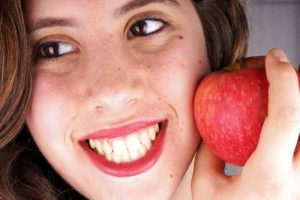 Close up of the face of a young lady with red apple