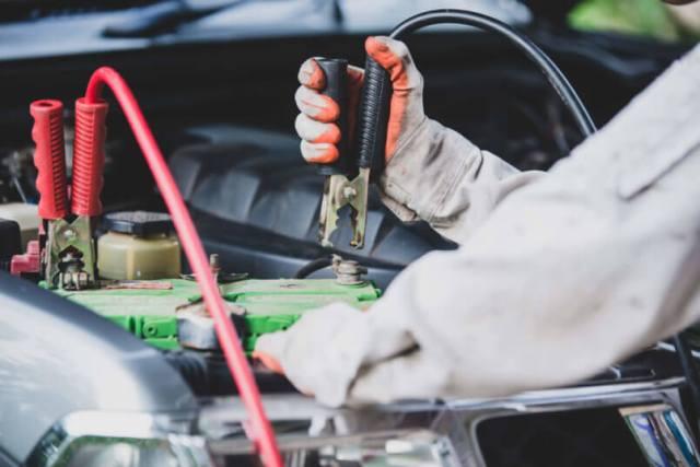 imagem de um mecânico testando a parte elétrica de um carro com problemas após pegar no tranco