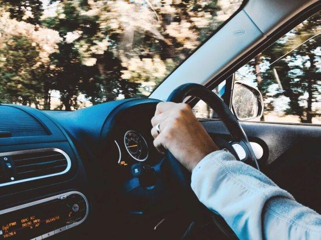 imagem de um motorista ao volante de um carro com uma boa bateria veicular