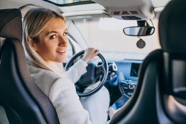 Imagem de uma motorista feliz em ter uma das melhores baterias de carro